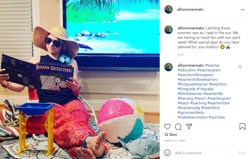 Teacher sitting in a chair surrounded by the accoutrements of a beach visit reading the book Shark Detective while in front of a TV screen featuring a beach scene