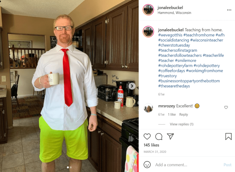 Teacher at home in his kitchen holding a mug and wearing bright green shorts along with shirt and tie