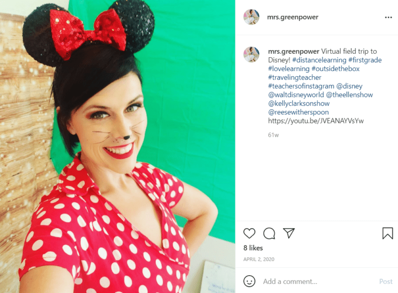 Teacher standing in front of a green screen in a red and white polka dot dress, Minnie Mouse headband, and dot on her nose