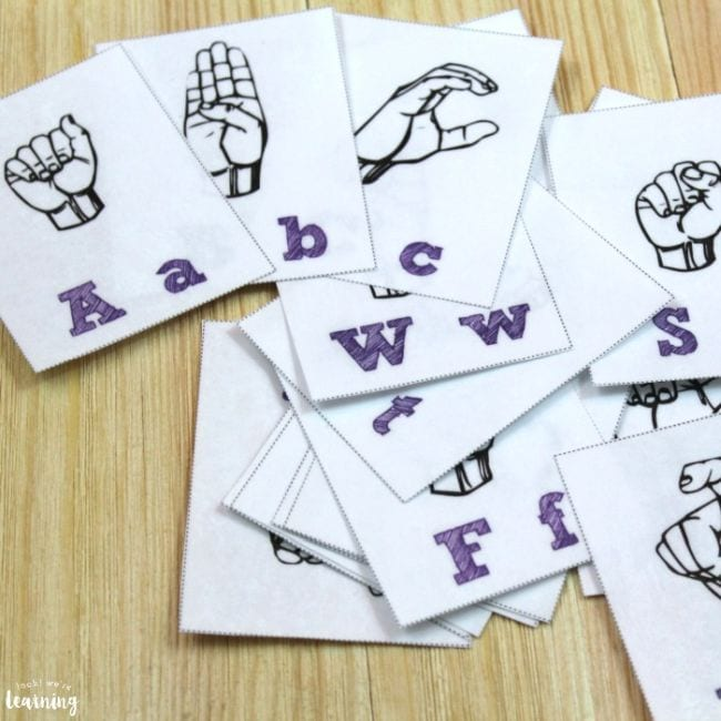 Black and white flashcards with alphabet letters and drawing of hands showing the signs for the letters