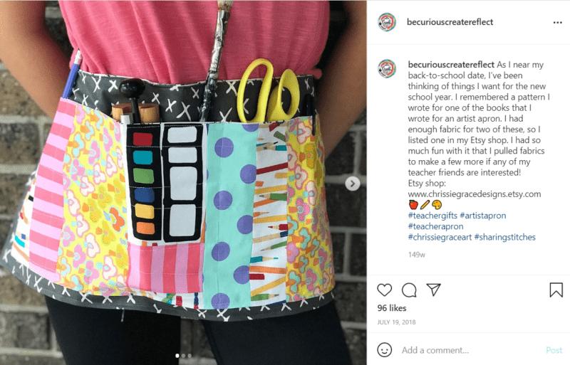 Torso of teacher wearing apron featuring cartoonish art supply designs