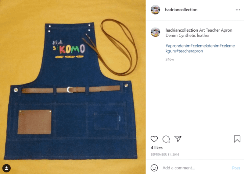 A blue denim full size apron with faux leather adornment and words in a foreign language spread out on a yellow floor