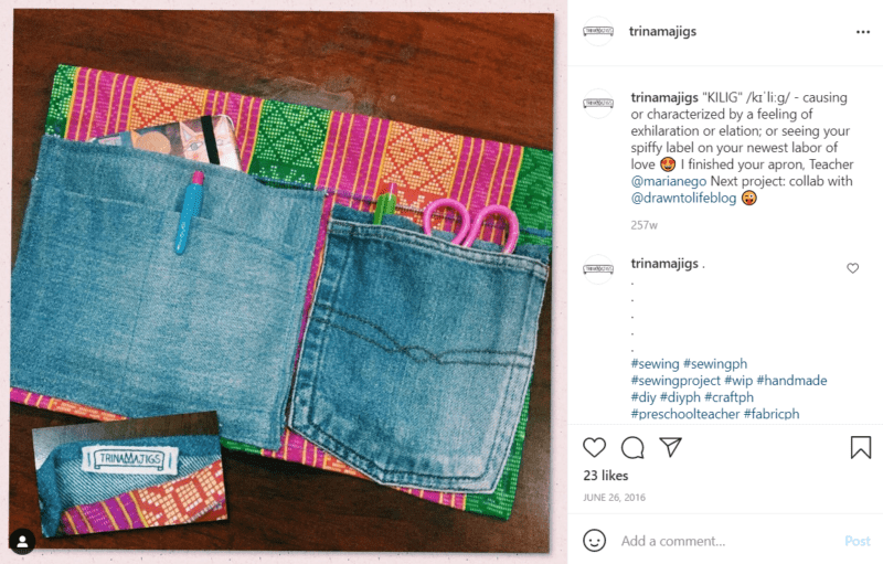 A teacher apron that has upcycled denim pants pockets and a patch is on a wood surface