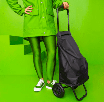 Women in all green outfit holding a black rolling bag
