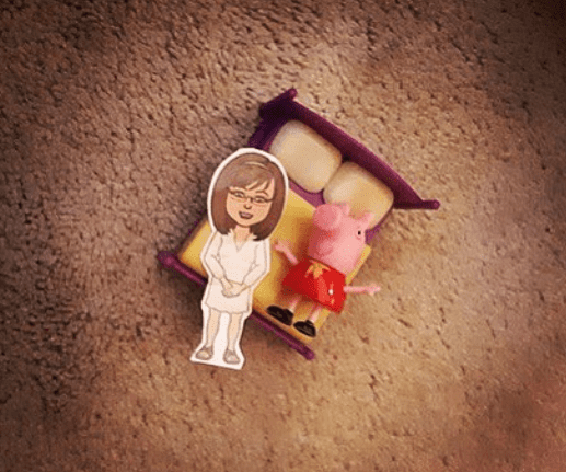 Flat Stanley teacher laid out against toy bed on carpet