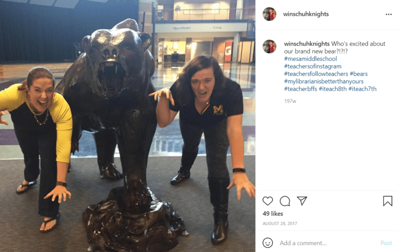 Two teachers on either side of a bear mascot statue in middle school