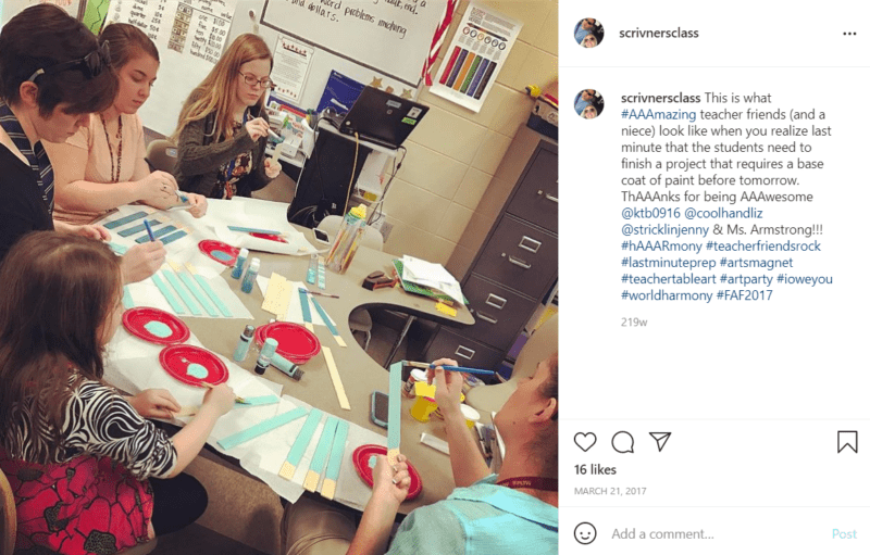 Teachers sitting at a table painting items for a student project