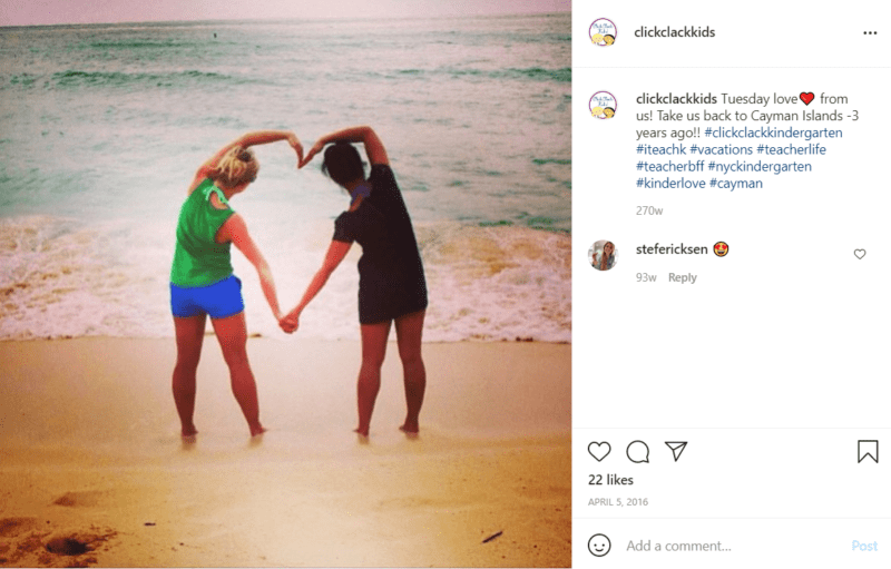 Two teachers posing with their arms to make a heart facing beach
