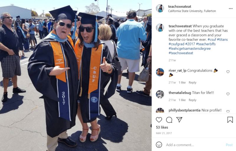 Two teachers in a parking lot wearing cap and gown for a graduation ceremony