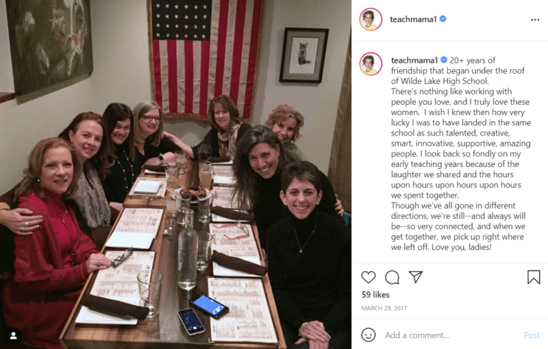 Eight teachers pose together at a table in a restaurant