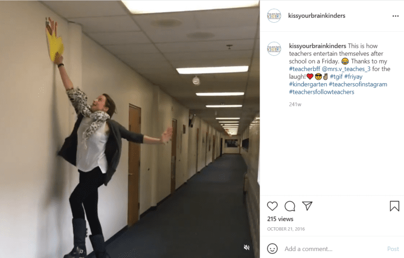 Teacher in a school hallway jumping to pull a decoration off wall