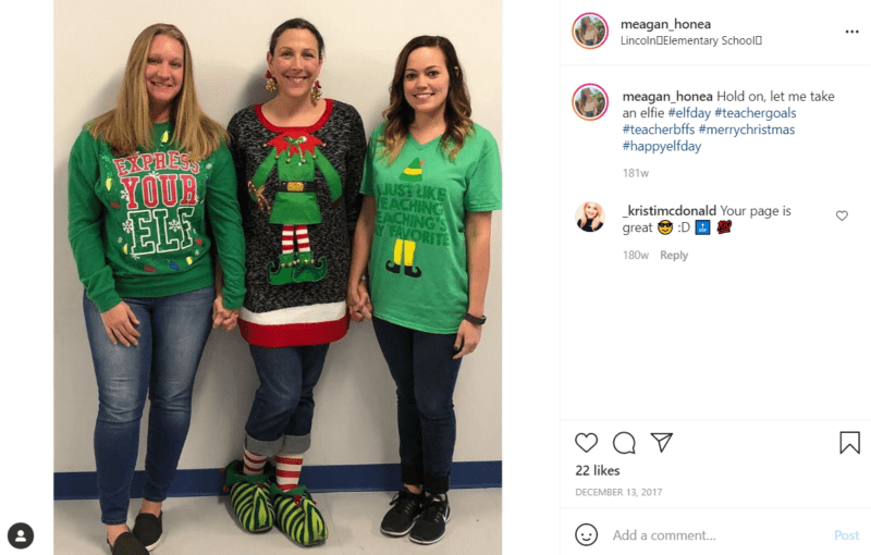 Three teachers pose in tacky Christmas sweaters in a school hallway