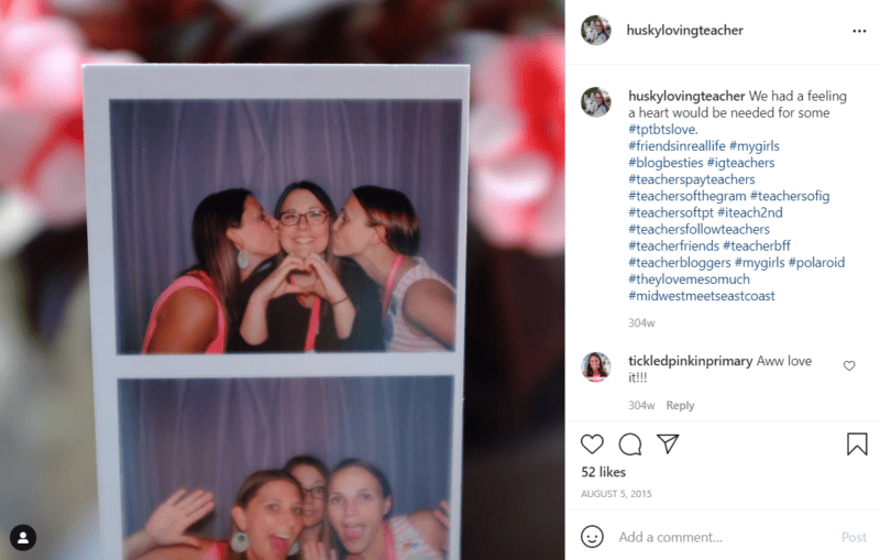 Three teachers in a photo booth kissing cheeks and making a heart with fingers