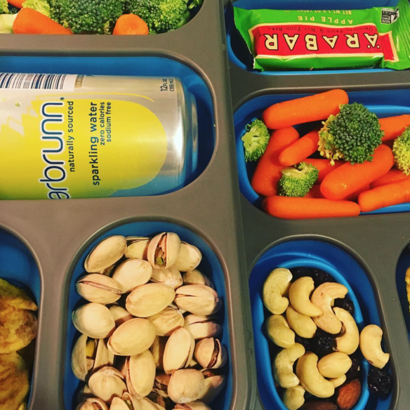 Pistachios, vegetables, and other snacks in a container