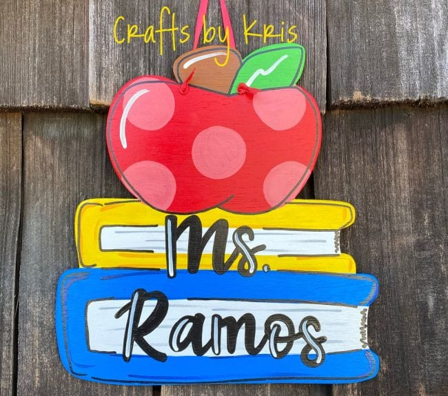 Wood sign depicting stack of books and an apple with teacher name printed on it (Teacher Name Signs)