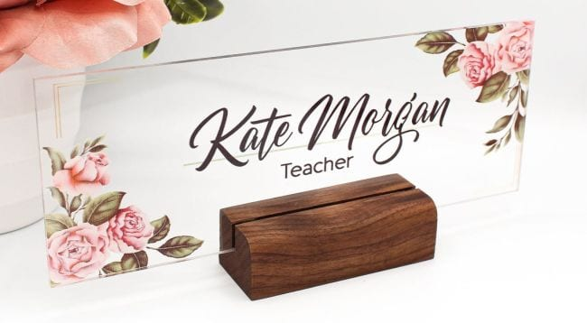 Clear acrylic name sign with floral decoration in the corners, mounted on a block of wood (Teacher Name Signs)