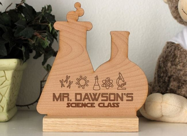 Wood sign in the shape of two lab beakers engraved with a teacher's name