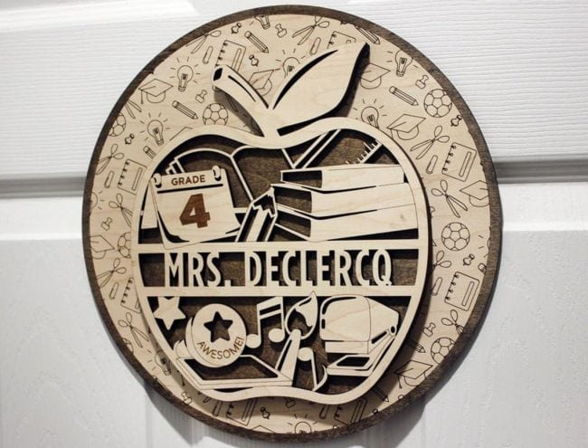 Laser cut sign of balsa wood in the shape of an apple, with a teacher's name and various symbols of education (Teacher Name Signs)