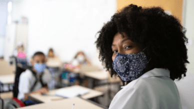 African American teacher wear mask in classroom practicing teacher self care with middle grade students wearing masks seated at desks behind her