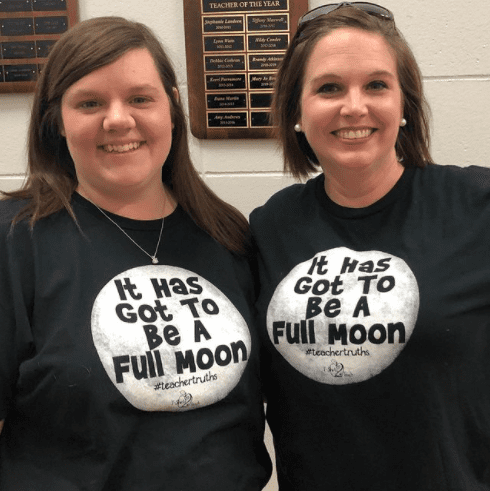 Two teachers in matching t-shirts.