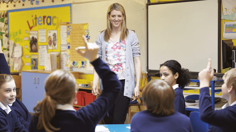 Teacher call students by name, hands wave in classroom.