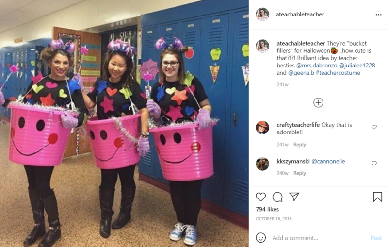 Three teachers in front of lockers in a school hallway each standing in a pink bucket with a smiling face draw onto it