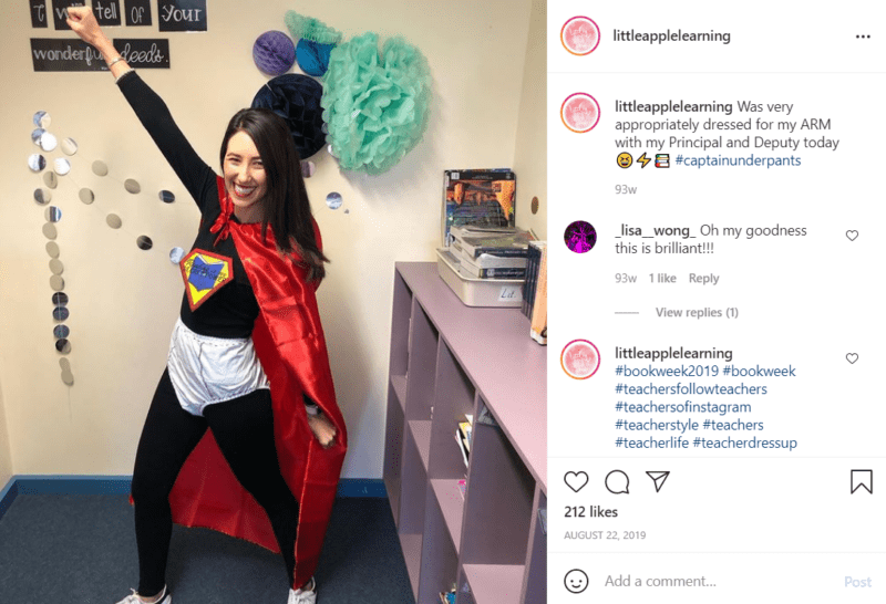 Teacher in a classroom striking a hero pose dressed as Captain Underpants