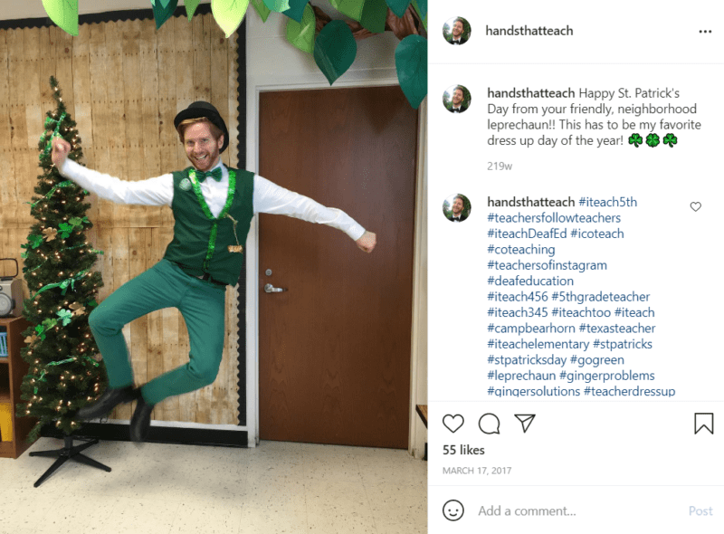 Teacher in a leprechaun outfit in a classroom jumping and clicking his heels in front of a Christmas tree with shamrock garland