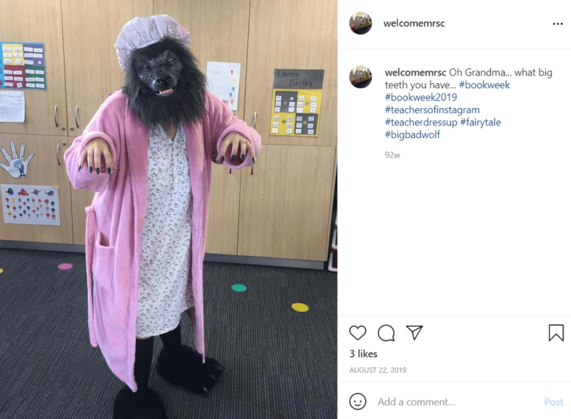 Teacher in a pink robe and wolf mask in a classroom
