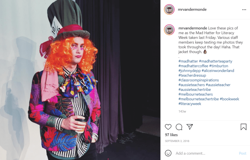 Teacher dressed as the mad hatter with black curtains in background