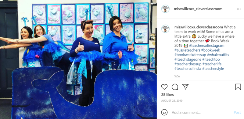 Four teachers wearing blue whale costumes in a classroom behind a cardboard cutout of a whale