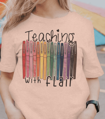 Teaching with flair tshirt with colorful pens pictured, as an example of Etsy teacher shirts