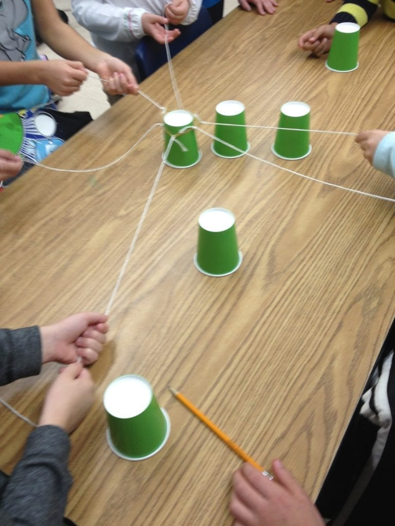 kids around a table playing a cup stacking game with paper cups and string