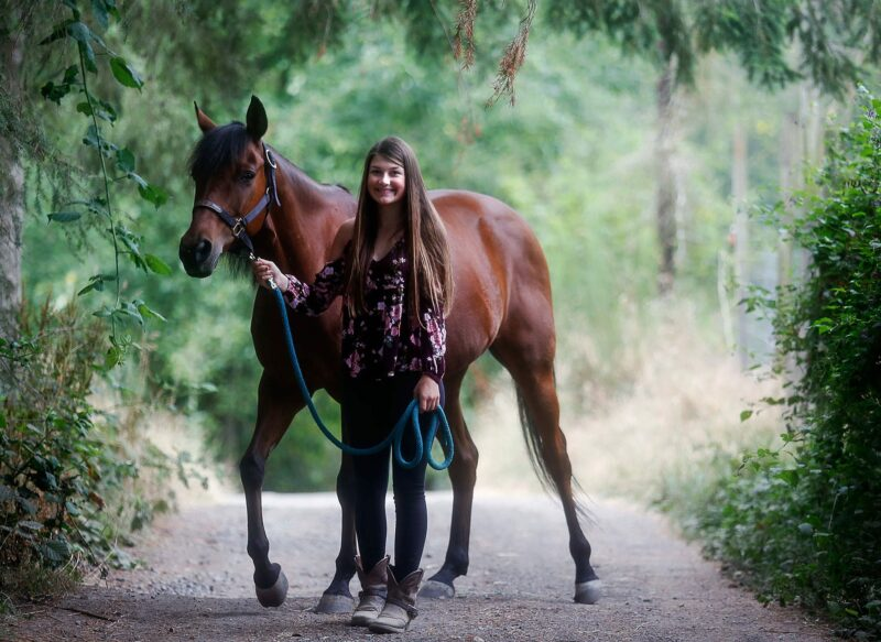 A teen girl and her horse standing in a lane