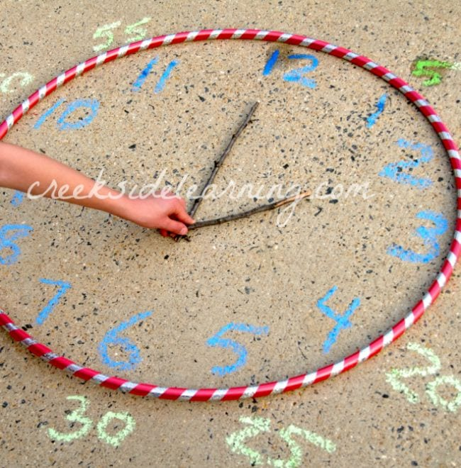 Student moving stick hands on a clock made from a hula hoop and sidewalk chalk markings