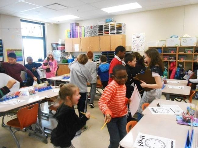 Students dancing around the classroom to look at paper clocks on each other's desks