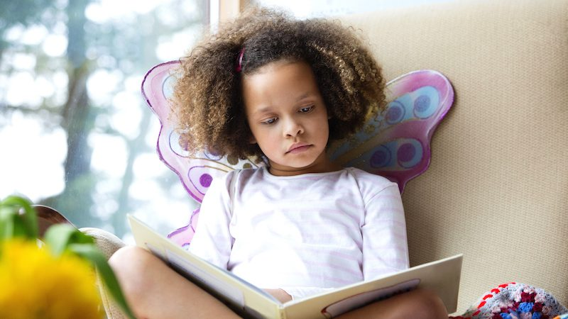Child in butterfly wings with a book on her lap
