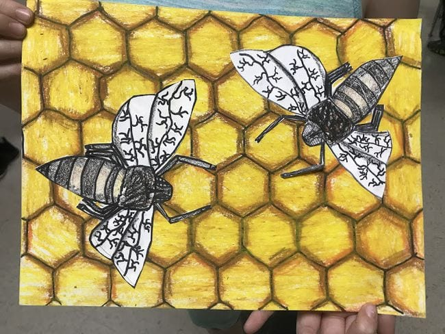 Yellow and brown honeycomb made from interconnected hexagons, with paper bees on top