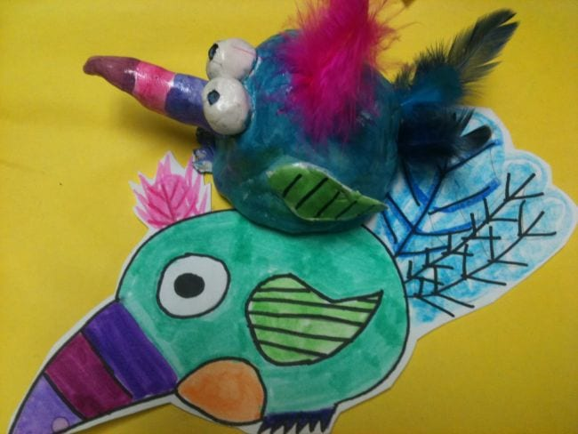 Drawing of a colorful bird, next to the same bird sculpted in clay with feathers added