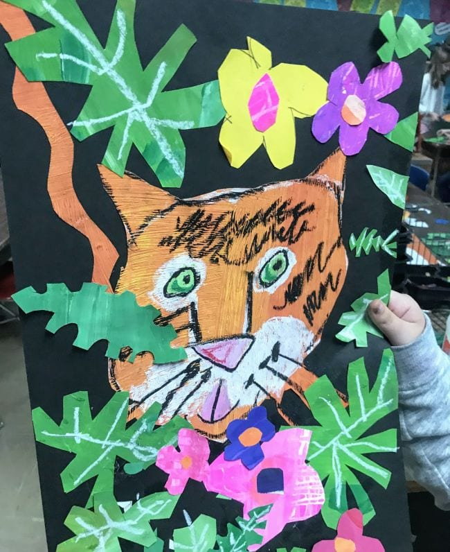 Textured painted tiger among construction paper leaves and flowers