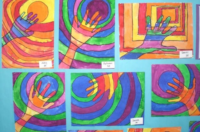 Tracings of hands with circles behind, colored in warm and cool colors (Third Grade Art Projects)