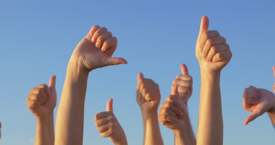 hands raised with thumbs extended