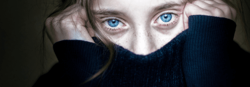 close up of traumatized girl with bright blue eyes covering mouth and nose with sweater during trauma informed teaching