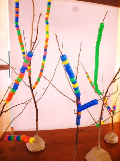 Twigs held upright with clay and strung with colorful plastic beads