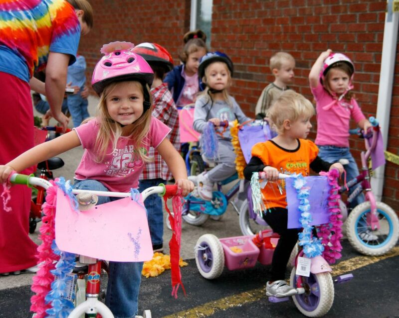 Colorfully dressed preschoolers riding decorated tricycles