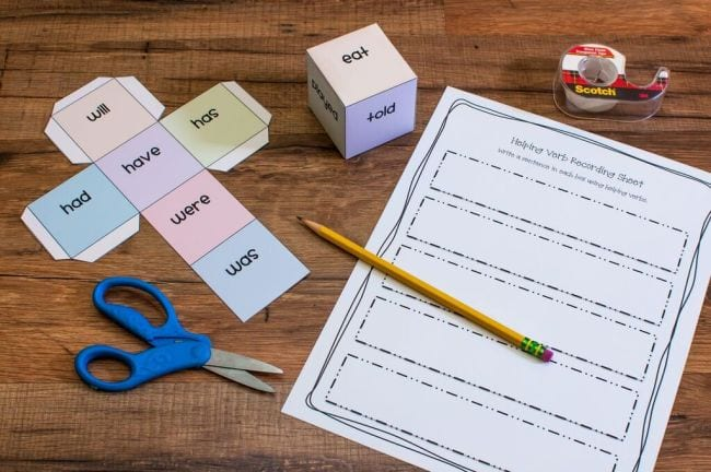 Paper cube with helping verbs on each side and a printable worksheet for writing sentences