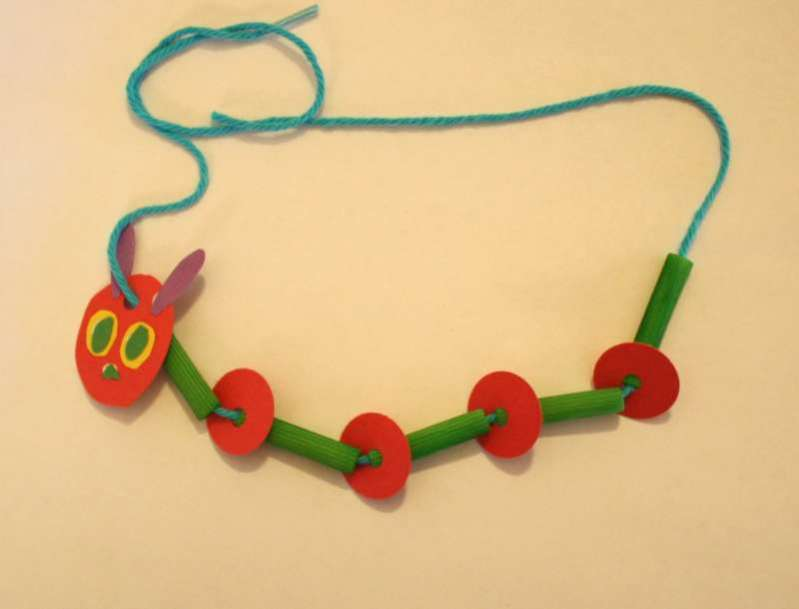 caterpillar necklace made from pasta noodles, paper discs and yarn