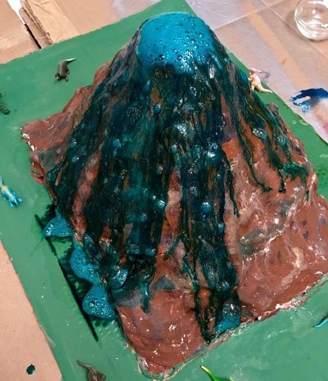 Papier-mâché model volcano erupting with blue lava