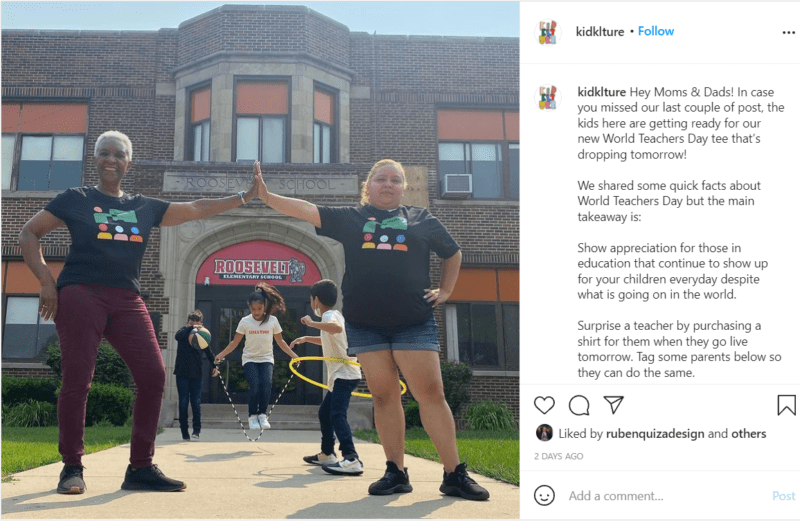 Two teachers stand outside of school giving a high five