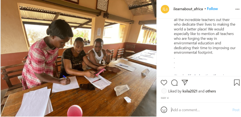 Teacher in Africa sitting at a table with two students doing work